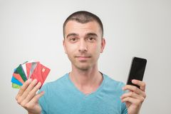 Close up portrait of young man in glasses holding a lot of gredit cards. Close up portrait of young man in glasses holding a lot of gredit cards and phone royalty free stock photo