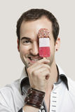 Close-up portrait of young man holding ice cream bar against gray background Stock Photography
