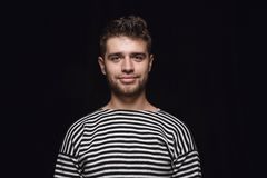 Close up portrait of young man isolated on black studio background stock photo