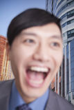 Close-up portrait of young man laughing, focus on background of building exteriors and skyscrapers Stock Photo