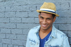 Close up portrait of a young man laughing on gray brick wall background Royalty Free Stock Photo