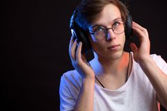 Close up portrait of young man listening to favourite song with attention. Isolated black background Stock Photos