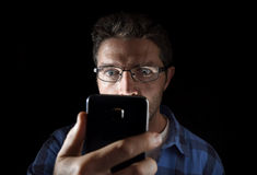 Close up portrait of young man looking intensively to mobile phone screen with blue eyes wide open isolated on black background royalty free stock image