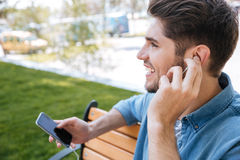 Close-up portrait of a young man sitting with mobilephone. Close-up portrait of a young man sitting with mobile phone and earphones outdoors in park Royalty Free Stock Photography