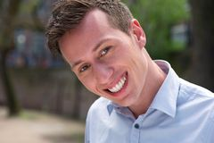 Close up portrait of a young man smiling outdoors. Horizontal close up portrait of a young man smiling outdoors stock image