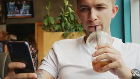 Close-up portrait of young man use mobile phone in cafe, drinks cold coffee cocktail stock video