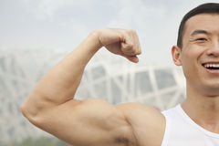Close-up portrait of young man in white tank top smiling and flexing his bicep royalty free stock image