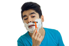 A close-up portrait of young man who stands with foam on your face and shaves his beard Stock Photo
