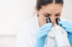 Close up portrait of young medical researcher looking through mi. Young woman medical researcher looking through microscope in laboratory, medicine concept Stock Photography