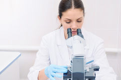 Close up portrait of young medical researcher looking through mi. Young woman medical researcher looking through microscope in laboratory, medicine concept Royalty Free Stock Image