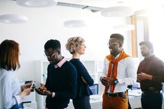 Close up portrait of young multi ethnic people talking in pairs. New methods of comunication in the office stock photos
