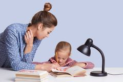 Close up portrait of young mum helps to write her daughter to write composition, use reading lamp, girls look concentrated, stock photo