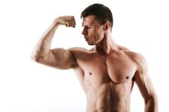 Close-up portrait of young muscular man with short haircut looking at his triceps. Isolated on white background stock image