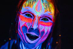 Close-up Portrait of Young naked bodyarted woman in blue glowing ultraviolet paint and Yellow eye lenses. Avatar entity stock image