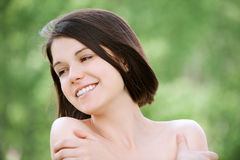 Close-up portrait of young pleasant. Dark-haired woman at summer green park Royalty Free Stock Photos