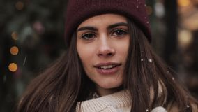 Close up Portrait of Young Pretty Caucasian Girl Wearing Winter Hat and Scarf, Standing in Falling Snowflakes Outside stock video