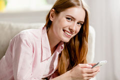Close up portrait of young pretty smiling woman, holding phone in her hands. Royalty Free Stock Photo