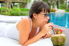 Close-up portrait young pretty woman drinking coconut cocktail Stock Photo