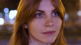Close- up portrait of a young red-haired attractive woman at night outdoors. Flashing lights from advertising signs. In Odessa stock footage