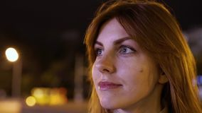 Close- up portrait of a young red-haired attractive woman at night outdoors. Flashing lights from advertising signs. In Odessa stock video