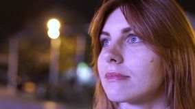Close- up portrait of a young red-haired attractive woman at night outdoors. Flashing lights from advertising signs. In Odessa stock video footage