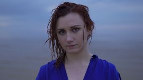 Close up portrait of Young redhead woman girl in a blue dress with wet hair - Moody cold sunset with vivid magenta. Close up portrait of Young redhead woman girl stock footage