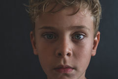 Close up portrait of young sad or depressed blonde boy with blue Royalty Free Stock Images