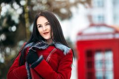 Close-up portrait of a young sexy girl hipster. Portrait amazing smiled winter young woman walking on street full with snow in sunny morning. Red telephone box Stock Image