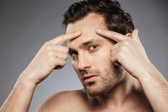 Close up portrait of a young shirtless man. Squeezing pimple on his face isolated over gray background stock photos