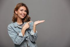 Close-up portrait of young smiling brunette woman pointing with. Finger on her empty palm, looking at camera,  over gray background Stock Photo