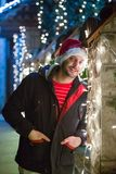 Close up portrait of young smiling man, with santa claus cap sta. Nding next to Christmas lights decoration Stock Image