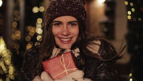 Close up portrait of young smiling pretty girl, looking happy, hugging gift box and smiling. Woman standing in falling stock footage