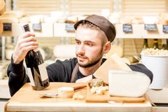 Cheese seller portrait. Close-up portrait of a young sommelier or cheese seller with cheese assortment and wine bottle in front of the store showcase stock images