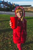 Close up portrait of young stylish smiling blonde girl in red clothes holding takeout red plastic cup in her hands. - Image. Close-up hand with red plastic cup stock images