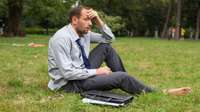 Close-up portrait of young unhappy businessman. He is sitting on a grass. Royalty Free Stock Image