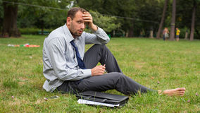 Close-up portrait of young unhappy businessman. He is sitting on a grass. Stock Photos