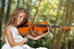 Close up Portrait of young violinist in woods. Royalty Free Stock Photo