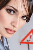 Close-up portrait of young woman. Close-up portrait of young brunette woman against warning sign Royalty Free Stock Photo