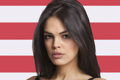 Close-up portrait of young woman against American flag Stock Photo