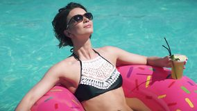 Close-up portrait of a young woman in a bikini. Beautiful girl in sunglasses drinks a soft drink lying on an inflatable. Young woman in swimsuit sunbathing lying stock footage