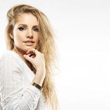 Close-up portrait of young woman. Portrait of a blonde young woman with beautiful flying curly hair and natural makeup in a white shirt Stock Images