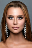Close up portrait of young woman with bronze smokey eyes. Wearing long earrings. Modern bridal make-up. Perfect brows. Studio shot Stock Photos