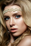 Close up portrait of young woman with bronze smokey eyes. Close-up portrait of young woman with bronze smokey eyes wearing white pearl hair band. Modern bridal Stock Photo