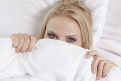Close-up portrait of young woman covering face with bed sheet Stock Images