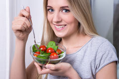 Close up portrait of young woman eating salad with tomatoes and Royalty Free Stock Image