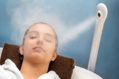 Young woman having thermal steam treatment on face stock image