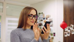 Close-up portrait of young woman in glasses use smartphone in the office. Text message, online surfing. App, social network stock video footage
