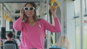 Close-up portrait of a young woman with headphones standing in the modern tram. A woman in glasses listens to music in a. Tram stock video