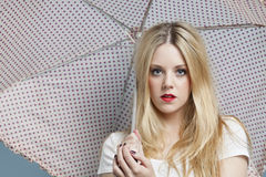 Close-up portrait of young woman holding polka dots umbrella Stock Photo