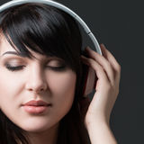 Close-up portrait of young woman listening to music Stock Photo